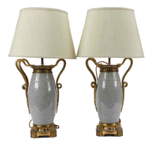 A pair of Chinese crackleglaze barrel shape vases, later gilt metal mounted as table lamps, having dual entwined snake side handles, the pierced socles with outset foliate cast square section feet, 44cm.