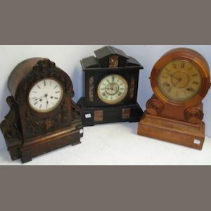 A Victorian walnut arched top mantel clock, foliate swag and scroll carved, the 8 day movement striking on a bell, stamped on the door 'James Hardy & Coy, 235 Brompton Road, London SW', Victorian architectural style marble and black slate mantel clock and a Victorian oak parquetry banded mantel clock. (3)