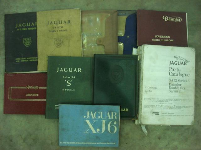 Nine Jaguar service books.