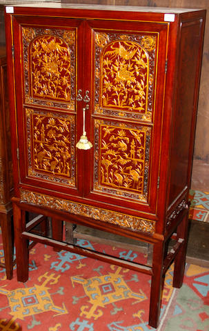 A modern Chinese carved hardwood and gilt heightened two door cabinet on stand,