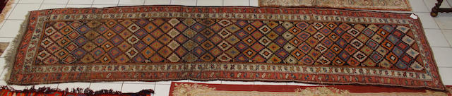 A North West Persian carpet,with a vari-coloured repeating stepped diaper field, 450 x 120cm and four Belough/Afghan rugs. (5)