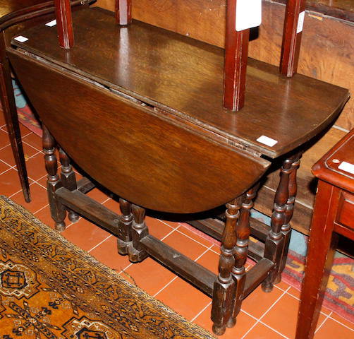 An oval oak gate-leg table,
