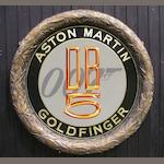 A hand-painted James Bond Goldfinger Aston Martin themed decorative roundel,