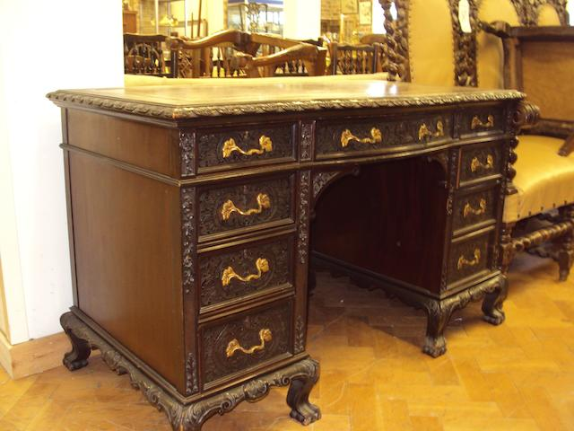 An Edwardian dark-stained and carved pedestal desk