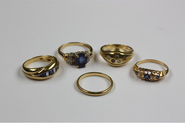 An 18ct gold dress ring, set with five vari-coloured diamonds, (un-tested), another 18ct ring set with oval fanzanite and four single cut diamonds, another set with vari-cut sapphires and two baguette diamonds, a plain 18ct gold band and a Victorian sapphire and diamond point ring. (5)