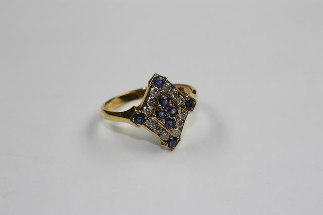 A dress ring, the lozenge panel set with eight circular cut sapphires and twelve single cut diamonds, the shank stamped '18ct'.