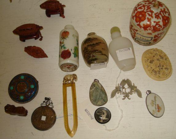A collection of Oriental objects to include, a glass snuff bottle interior painted, another, a Chinese foliate carved and pierced oval ivory plaque, a small circular bowl and cover, foliate painted in iron red, a circular filigree buckler style brooch, enamelled and set with turquoise cabochons, three pendants, carved jade brooch, two nuts carved as boats on wood stands and other stems.
