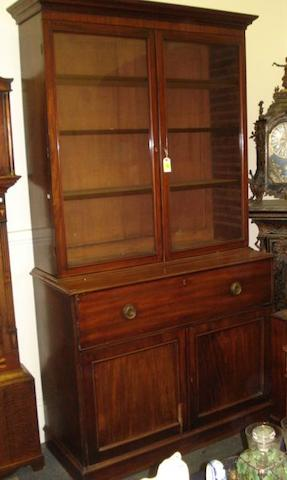 A George IV mahogany secretaire bookcase, the moulded cornice above adjustable shelves enclosed by a pair of glazed doors, the projecting base with a dummy drawer hinged fall front enclosing an arrangement of small drawers, 'secret' compartment pilasters, pigeon holes and central cupboard, cupboard below enclosed by a pair of panel doors on a plinth base, 127cm.