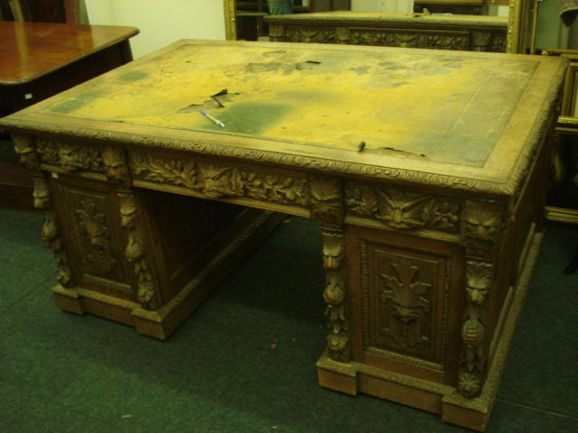 A partner's Victorian oak desk, of panelled construction, heavily carved with masks, oak leaves, acorns, flowers and fruits, the inset rectangular top above three frieze drawers and six pedestal drawers enclosed by a pair of doors, opposed by three frieze drawers and a pair of cupboards fitted with sliding trays, on inverted breakfront plinth bases, 153 x 100cm.