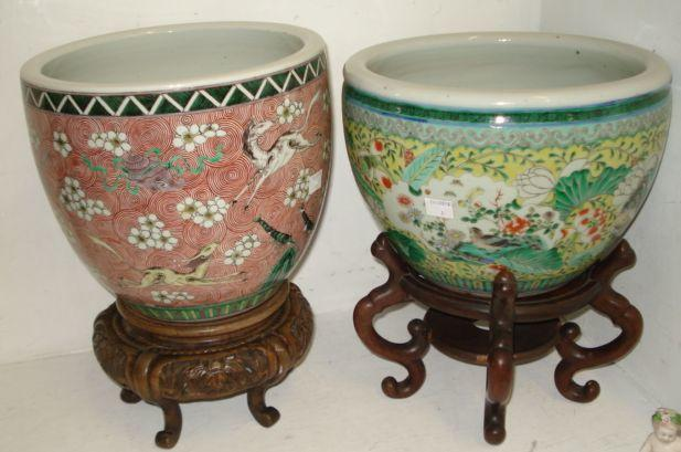 An early 20th Century Chinese planter bowl, decorated in a famille verte pattern, 29cm, another decorated with running animals on a red spiral ground, and two wooden stands, 26cm.