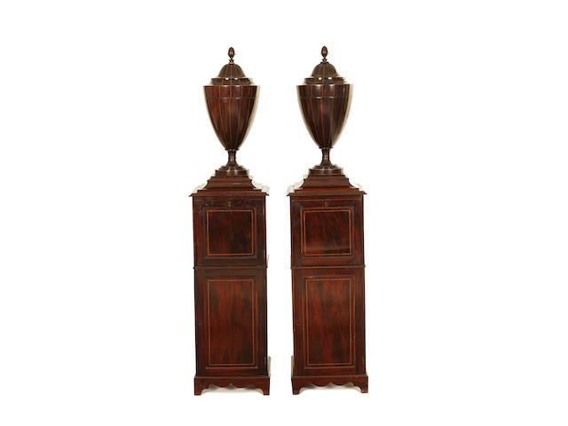 A pair of late 19th century Sheraton revival knife urns on pedestals