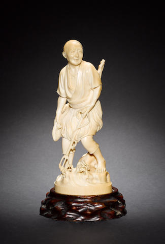 An ivory okimono, carved as a standing fisherman, holding a trident