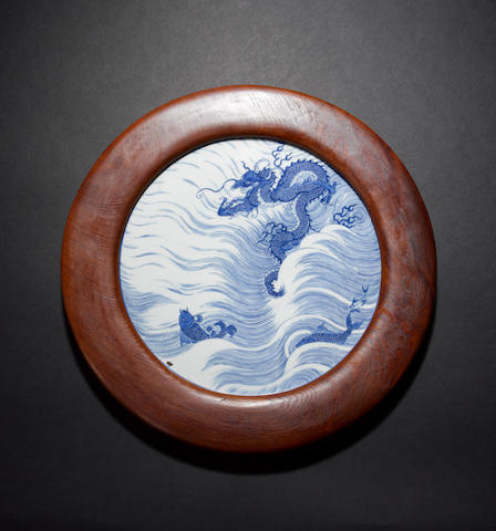 A blue and white plaque of circular form decorated with a Dragon beside two Carp, leaping above waves Kangxi six-character mark and of the period
