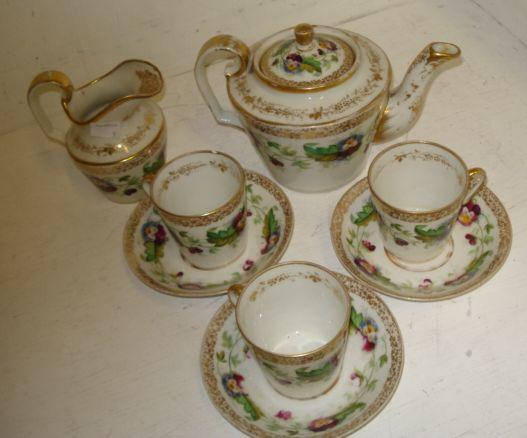 A Russian porcelain tea service, circa 1880, each piece painted with a band of pansy's within a gilt grape and vine boarder, comprising: teapot and cover, milk jug, nine cups and eight saucers. (19)