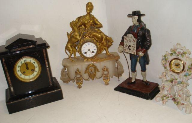An ornate 19th Century French gilt metal mantel clock, modelled as Diana the Huntress seated on the drum cased 8 day movement, the onyx plinth of shaped outline gilt metal mounted, 35cm, a Victorian black slate and marble 8 day mantel clock, an ornate continental porcelain cased timepiece, and a reproduction novelty painted metal figural timepiece. (4)