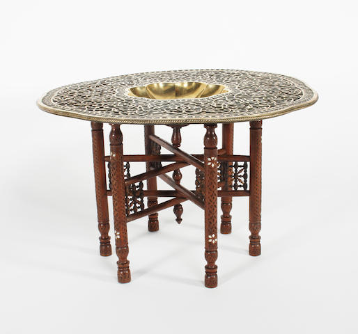 An Indian polished octafoil brass tray type table, School of Art, Jeypore, and folding stand, early 20th century
