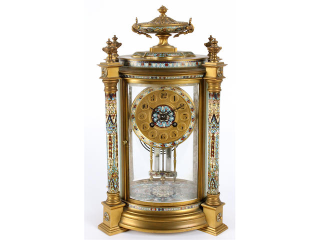 A late 19th/early 20th century French gilt brass and polychrome champleve oval section mantel clock