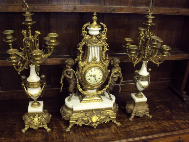 A reproduction gilt-metal and spelter mantel clock with candelabra garniture
