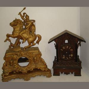 A late 19th Century oak and ebonised cuckoo clock case, 42cm, and a late 19th Century ornate gilt speltar mantel clock case decorated with trophies of war and surmounted by a knight in armour on horseback, together with a gilt gesso plinth. (3)