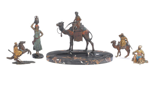 A cold painted bronze of a camel rider on a marble base