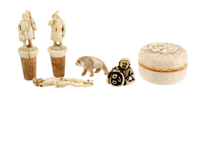 A pair of German ivory mounted cork bottle stoppers, 19th Century, each carved in the form of a dwarf, the ivories, 6cm, a carved ivory figure of Christ, originally pined to a cross, 8cm, a figure of an animal, a Netsuke carved as a seated figure, signed and a Japanese ivory circular box, Meiji, the pull-off cover carved with flowers, 6.5cm, signed. (6)