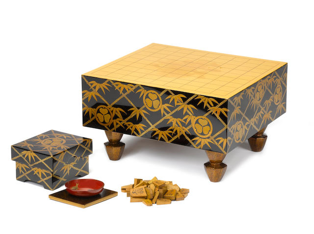 A lacquered-wood bento-bako (lunch box) in the form of a shogi-ban (Japanese chess games board) with a complete set of koma (chess pieces) and sakazuki (sake cup) Meiji/Taisho Period