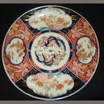 A Japanese Hizen Imari plate, Meiji, painted with segmented floral and bird panels, 37cm.