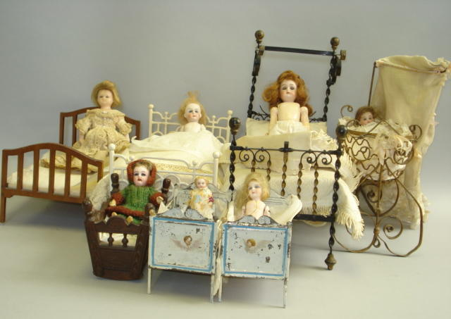 Various miniature dolls in beds lot