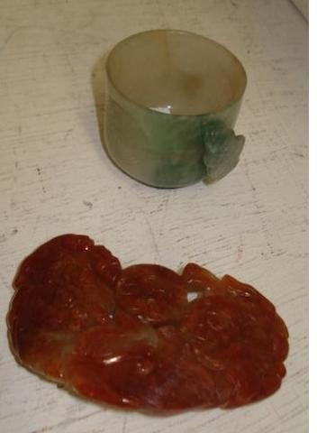 A mottled jadeite cup, the handle carved as a bat, 4cm, high, together with a mottled jade belt buckle carved with two Buddhistic lions with a ball. (2)