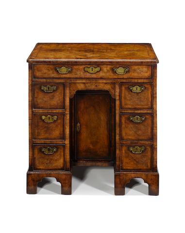 A George I figured walnut, featherbanded and crossbanded kneehole desk