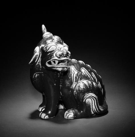 A mottled maroon/flambe glazed figure of a seated mythological animal