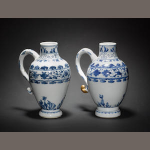A pair of blue and white ewers; each one with a loop handle