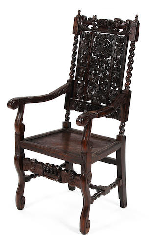 A Charles II style carved oak open armchair