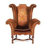 A William and Mary style beech and upholstered wing armchair