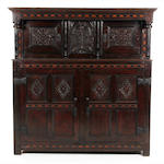 A carved and inlaid oak court cupboard