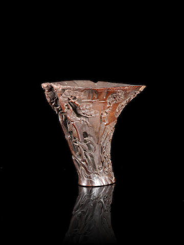 A dark rhino libation cup with inscription, wood stand