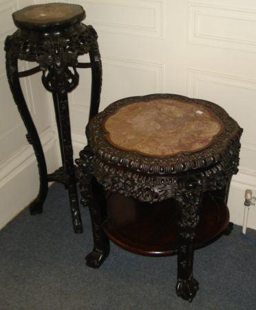 A Chinese foliate carved rosewood circular two tier cache pot stand, Qing dynasty, late 19th Century, with rouge royale marble inset top, on mask headed legs, with ball and claw feet, 63cm, and a taller similar example, on cabriole legs, 33cm. (2)