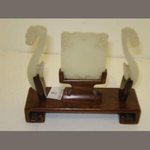 A carved jade panel, and a pair of belt hooks of grey white colour, the panel with pierced and carved border and incised with horses and script 5.5 x 5cm the hooks with carved dragons heads with purpose carved stand.(4)