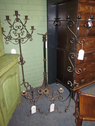 A collection of four wrought iron candelabra