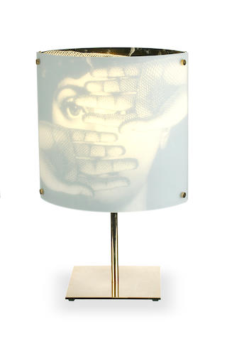 Piero Fornasetti (1913-1988) A 'Themes and Variations' table lamp the rounded square glass shade with printed face to each side, on a square brass base
