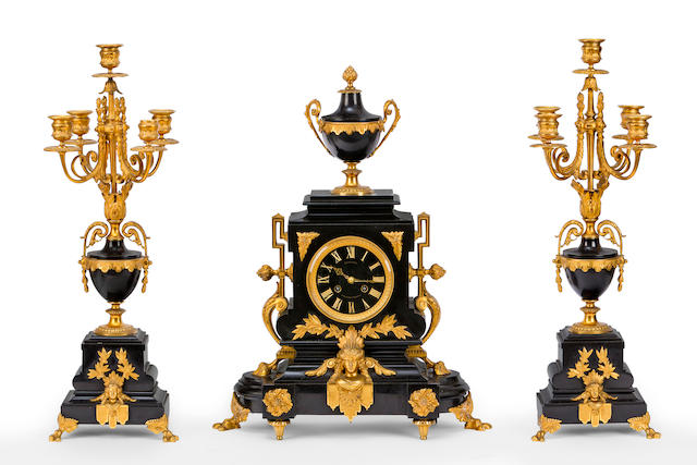A mid 19th century black marble and gilt bronze mounted mantel clock garniture
