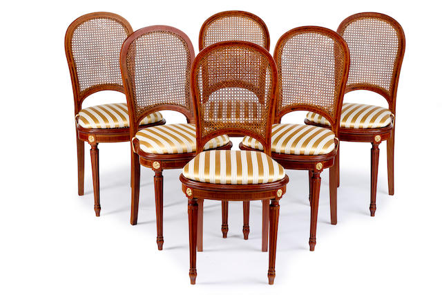 A set of twelve Louis XVI style satinwood and caned dining chairs