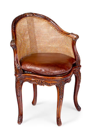 A Louis XV style walnut and caned fauteuil de bureau