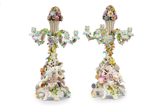 A pair of Meissen style porcelain figural flower encrusted candelabra