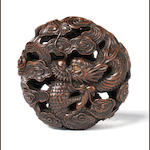 A wood netsuke of a manju pierced with a dragon