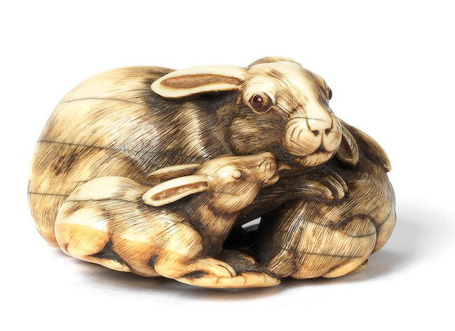An ivory netsuke of a hare and two leverets Attributed to Tomotada, Kyoto, late 18th century