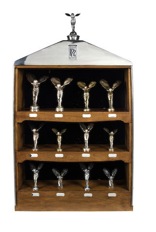 An impressive pre-War Rolls-Royce radiator display cabinet fitted with twelve Spirit of Ecstasy mascots from 1911 to 1939,