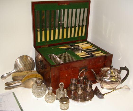 An Old English pattern canteen, in mahogany case with hinged top and two drawers under, electroplate soup ladle, teapot, egg cruet, four various silver mounted cut glass dressing table bottles and jars and a five piece engine turned silver backed dressing table set.