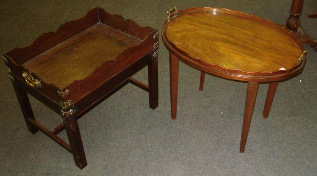 A George III butler's mahogany tray, with undulating gallery and brass carrying handles, on a later stand with square chamfered legs, 62cm, and an oval similar with brass side carrying handles, on later stand, 71cm. (2)