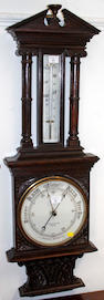 A late Victorian carved oak cased aneroid barometer,by G Cartwright and Sons Preston, 114cm and a convex wall mirror, 50cm diameter (2)